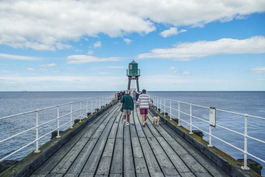 Man walking down ax pier with blue sea surrounding it